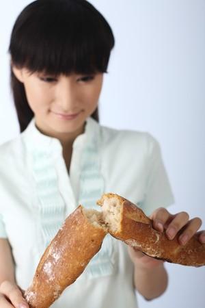 Woman breaking baguette into half photo