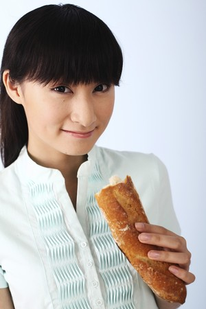 Woman smiling while holding baguette photo