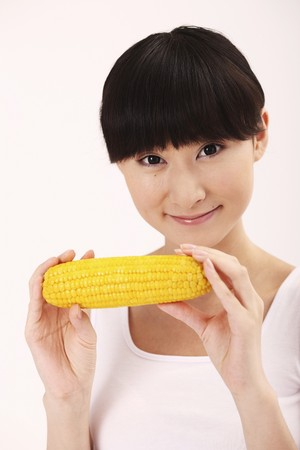 Woman smiling while holding corn on the cob photo