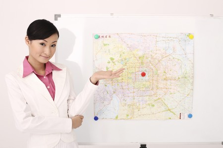 Businesswoman standing next to map with her arm outstretched Stock Photo - 4197445