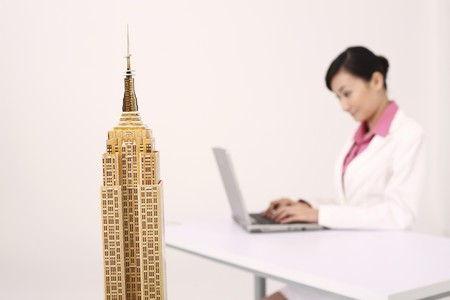 Focus on empire state building model, businesswoman using laptop in the background photo