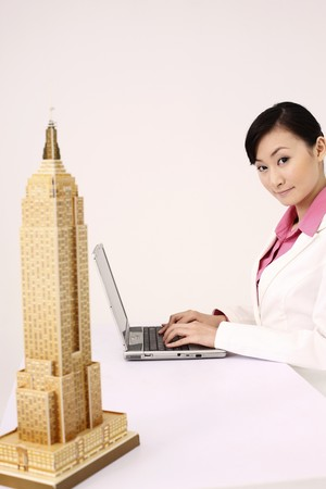 Empire state building model, businesswoman using laptop in the background Stock Photo - 4197402