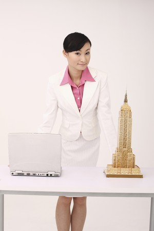 Businesswoman posing, laptop and empire state building model on the table photo