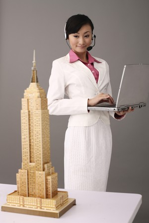Woman with telephone headset using laptop, empire state building model on the table photo