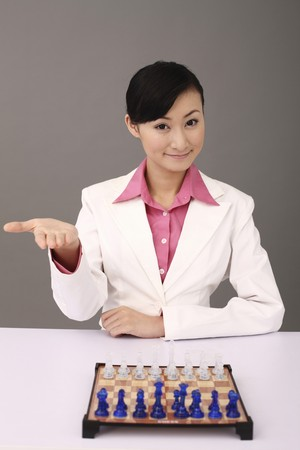 Businesswoman with chessboard and chesspieces on the table Stock Photo - 4197499