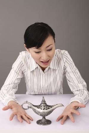 lampe magique: Businesswoman regardant lampe magique Banque d'images