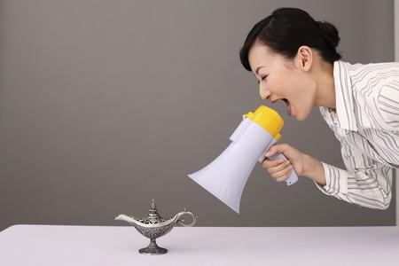 lampada magica: Businesswoman gridando a lampada magica attraverso megafono Archivio Fotografico