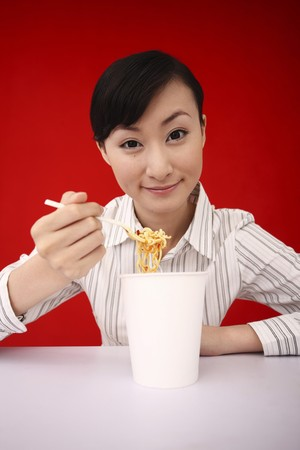 Businesswoman enjoying instant noodles Stock Photo - 4197486