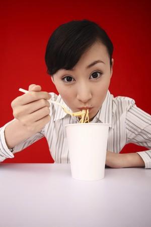 Businesswoman enjoying instant noodles photo