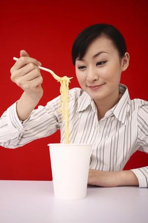 instant noodles: Businesswoman enjoying instant noodles