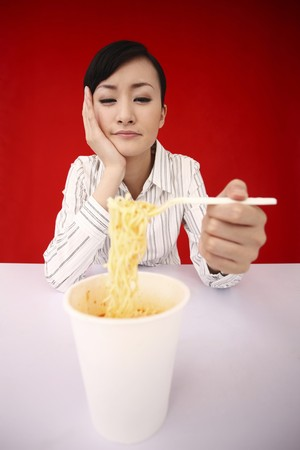 Businesswoman looking at instant noodles with a sad face photo