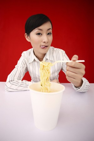 Businesswoman sticking her tongue out while preparing instant noodles Stock Photo - 4197466