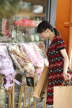 paperbags: Woman looking at gifts while carrying paperbags Stock Photo