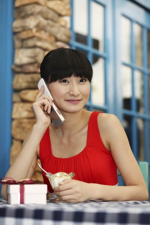 Woman talking on the phone while enjoying ice-cream photo
