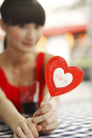 Woman holding heart shaped lollipop Stock Photo - 4197671