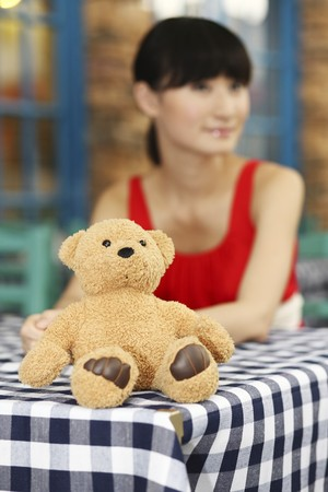 Teddy bear sitting on the table, woman in the background photo