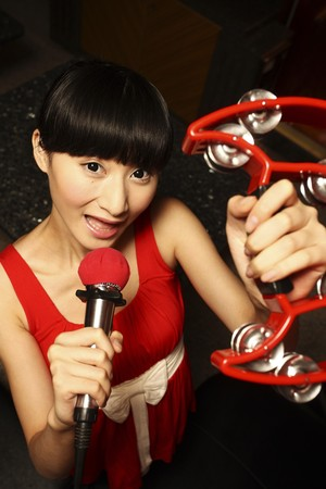 Woman playing tambourine while singing into microphone photo