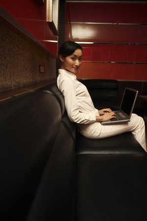 Businesswoman smiling while using laptop Stock Photo - 4197572