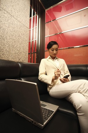 Businesswoman using PDA phone, laptop beside her photo