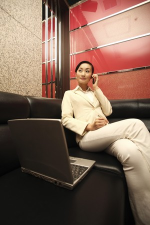 beside: Businesswoman talking on the phone, laptop beside her Stock Photo