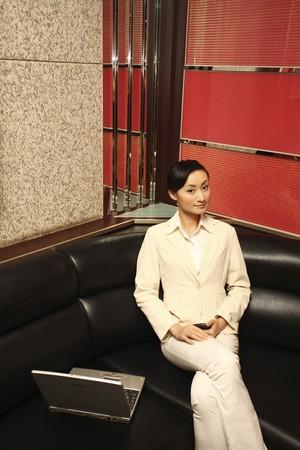 Businesswoman holding cellphone, laptop beside her Stock Photo - 4197675