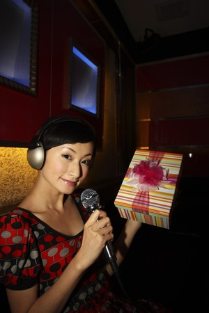 Woman with headphones singing into microphone while holding a box of gift photo
