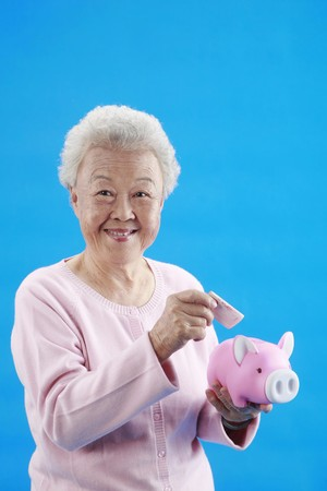 Senior woman about to put banknote into piggybank photo