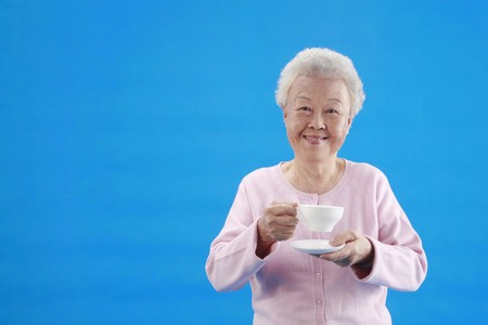 Senior woman holding a cup of coffee photo