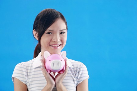 Woman smiling while holding piggybank photo