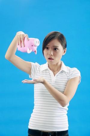 Woman turning her piggybank upside down photo