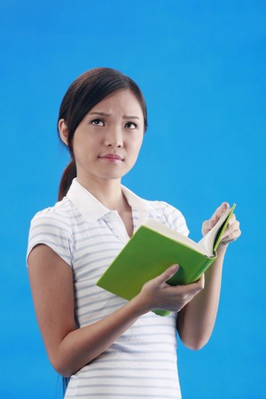 revision book: Woman looking up while holding book
