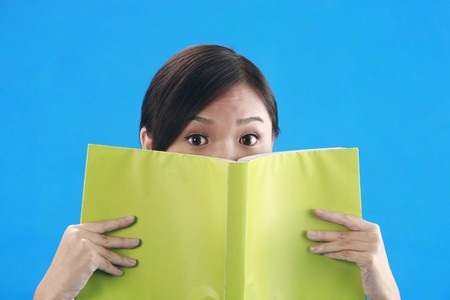 revision book: Woman covering her face with book Stock Photo