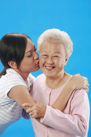 Woman kissing senior woman photo