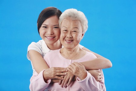 granddaughters: Woman hugging senior woman from the back