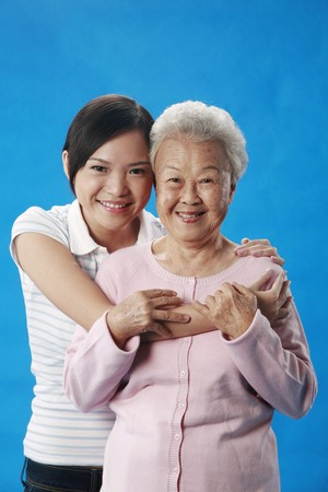 Woman hugging senior woman from the back photo