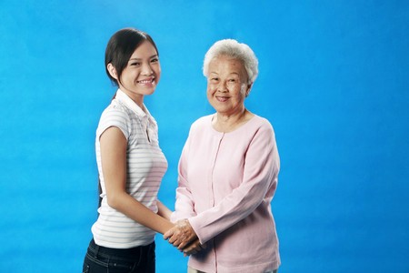 Woman and senior woman holding hands photo