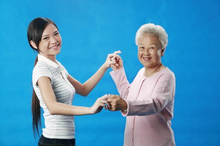 Woman and senior woman holding hands and dancing photo