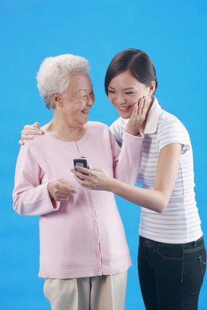 Woman showing the message on cellphone to senior woman photo