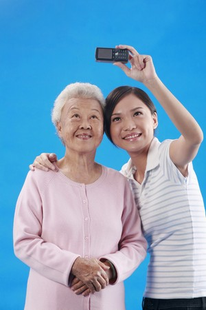 Woman and senior woman taking picture with camera phone photo