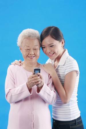 Woman and senior woman reading message on cellphone together Stock Photo