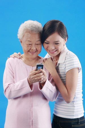 Woman and senior woman reading message on cellphone together Stock Photo - 4197630