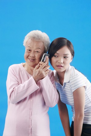 Woman and senior woman listening to phone conversation photo