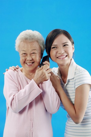 Woman and senior woman listening to phone conversation Stock Photo - 4197621