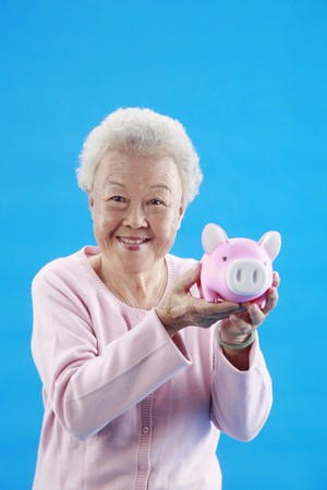 Senior woman smiling while holding piggybank photo