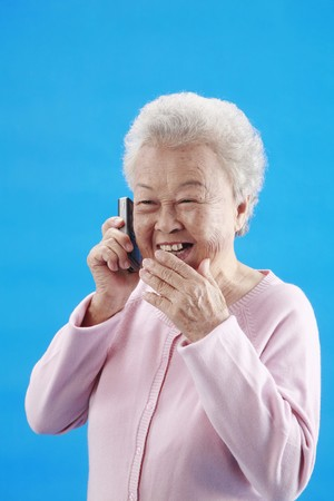 Senior woman laughing while talking on the phone