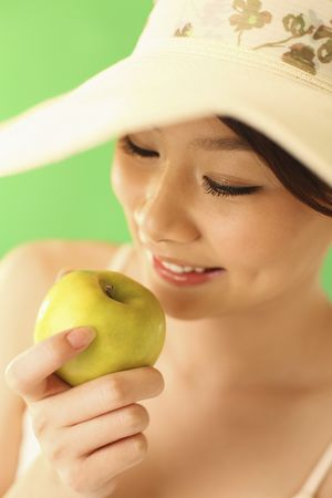 Woman holding a green apple, smiling photo