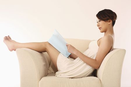 Woman sitting on the couch reading book Stock Photo