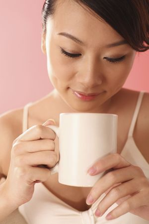 Woman holding a cup of coffee, smiling photo