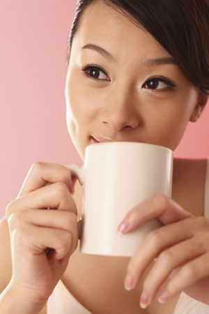 Woman holding a cup of coffee, contemplating photo