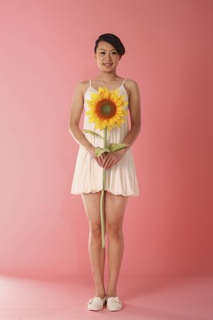 Woman holding sunflower, smiling photo